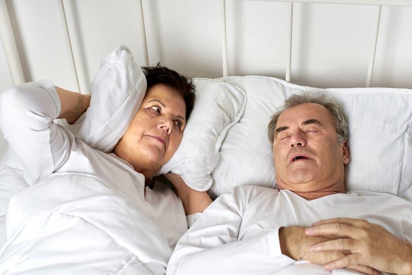 Senioren im Bett, Mann schnarcht, Frau ist genervt